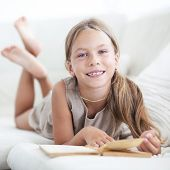 foto of 7-year-old  - Portrait of 7 years old child reading book on the sofa at home - JPG