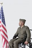 image of military personnel  - Young US soldier in wheelchair looking at American flag over gray background - JPG