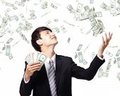 stock photo of bundle money  - happy business man earned dollar bills us money under a money rain  - JPG