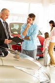 Young man listening to car agent in showroom