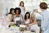 stock photo of bridal shower  - Middle aged woman taking pictures of friends at bridal shower - JPG