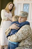 stock photo of soldiers  - Loving soldier embracing son before departing while mother looking at them - JPG