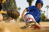 stock photo of softball  - Full length of softball player sliding into home plate - JPG