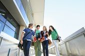 stock photo of angles  - Low angle view of four university students on campus - JPG