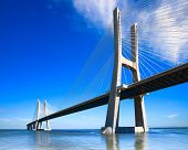 stock photo of nationalism  - Vasco da Gama bridge spans the Tagus River in Lisbon Portugal - JPG