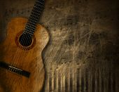 stock photo of string instrument  - Acoustic brown guitar against a grunge brown background - JPG
