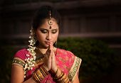 stock photo of diwali  - Portrait of beautiful young Indian woman in traditional sari dress praying in a hindu temple - JPG