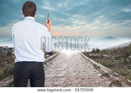Thinking businessman holding pen against stony path leading to misty mountain range