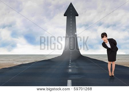 Surpised businesswoman bending against road turning into arrow