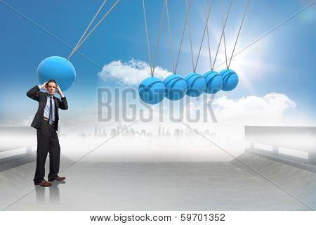 Stressed businessman with hands on head against newtons cradle above city