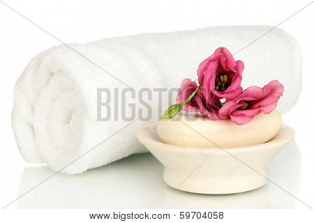Rolled white towel, soap bar and beautiful flower isolated on white