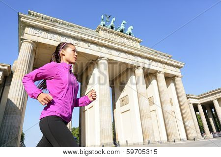 Running woman in Berlin, Germany by Brandenburg Gate jogging living healthy lifestyle. Female runner jogging. Urban fitness girl working out outdoors in jacket.