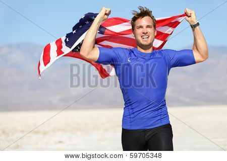 Success - winning runner cheering with USA flag celebrating victory. Fit American male winner fitness running model in celebration of success win. Face expression showing successful achievement.
