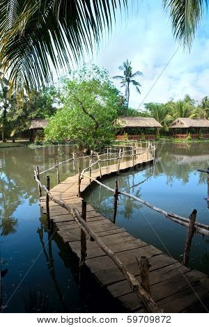 Wooden Bridge Over A Lake In Tropical Park