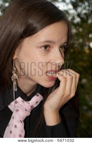 Uma menina que morde as unhas em desespero