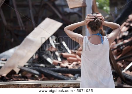 Woman Stands In Front Of Burned Out House