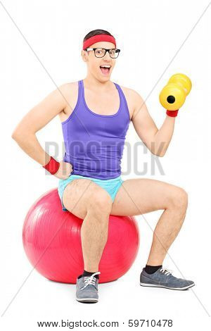 Nerdy guy sitting on pilates ball and lifting a dumbbell isolated on white background