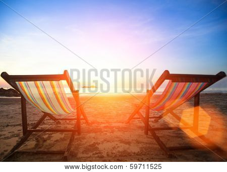 Couple of beach chairs on the evening sea coast.