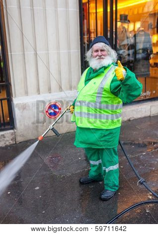 PARIS, FRANCE - JANUARY 4, 2012: Elderly worker washes street with mini wash. Paris is one of the very few cities in the world with a dual water system.