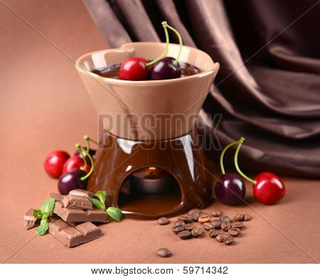Chocolate fondue with fruits, on  brown background