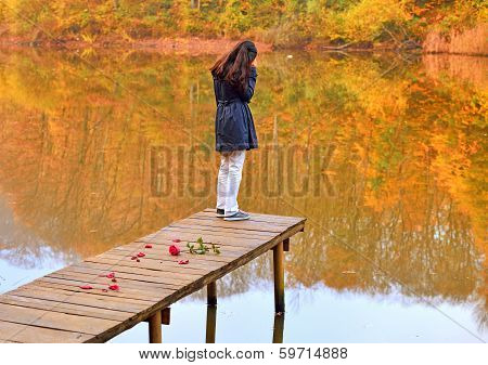 unhappy young girl on wooden bridge