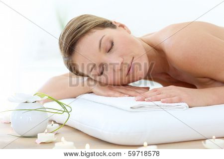 Attractive woman relaxing with eyes shut on massage bed