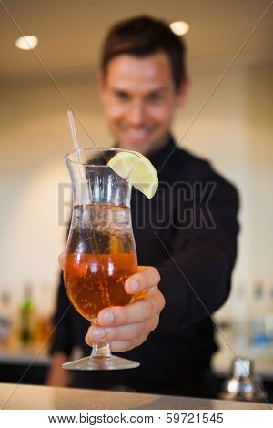 Happy bartender offering cocktail to camera at the bar