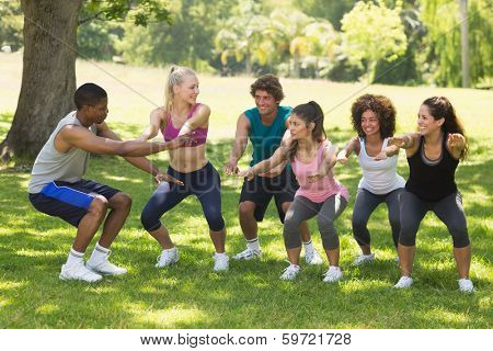 Instructor with group of fitness class exercising in the park