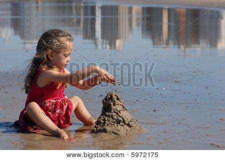 Girl Playing With Sand On The Beach