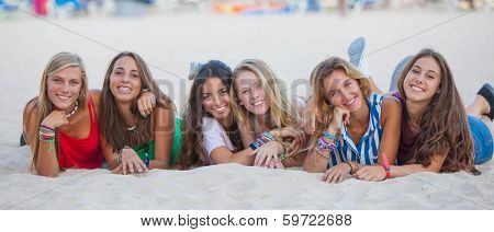 mixed race group of happy summer teens on beach