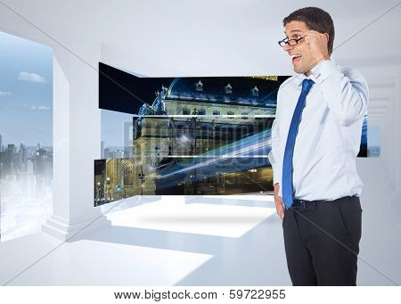 Thinking businessman tilting glasses against bright white hall with columns