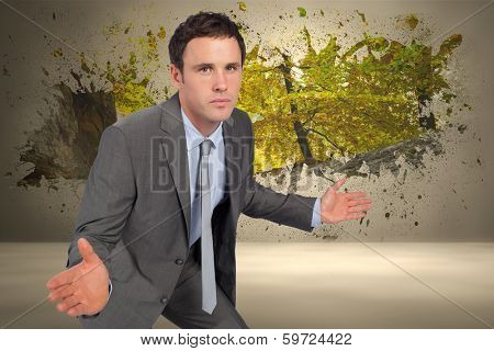 Businessman posing with hands out against splash on wall revealing forest trail