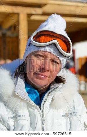 Middle-aged Woman In A White Jacket And Ski Goggles