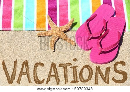 Vacation beach travel text concept. VACATIONS written in sand with water next to beach towel, summer sandals and starfish. Summer and sun vacation holidays.