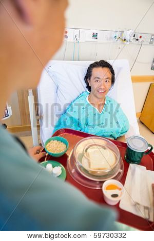 Mature smiling patient looking at nurse serving breakfast in hospital