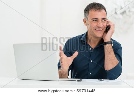 Portrait Of Happy Mature Man In Front Of Laptop Talking On Cellphone
