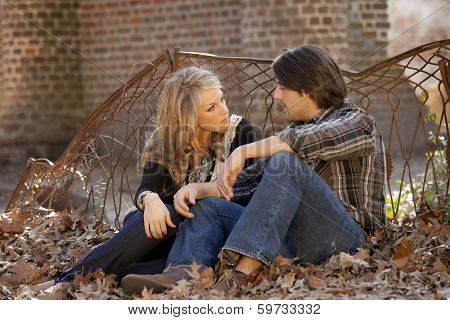 handsome young couple having conversation seated in leaves