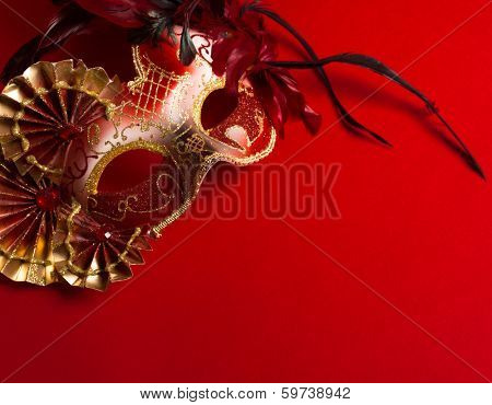 A red and gold venetian, mardi gras mask on a red bakground