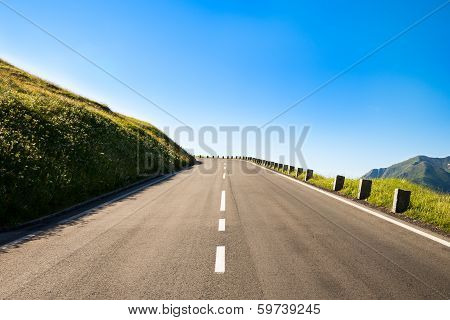 Empty Country Road With A Sharp Left Curve In The Brow Of A Hill