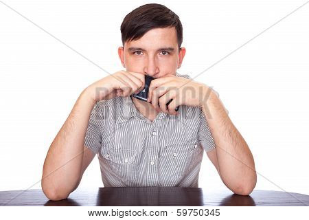 Man holding a smartphone near mouth an thinking