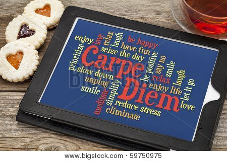 Carpe DIem and positivity word cloud on a digital tablet with tea and heart cookies