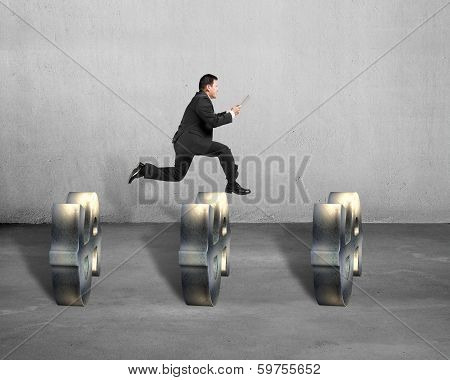 Businessman Jumping Over Money Symbols