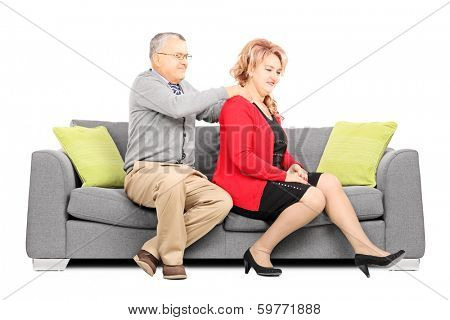 Mature man giving a back rub to his wife seated on couch isolated on white background