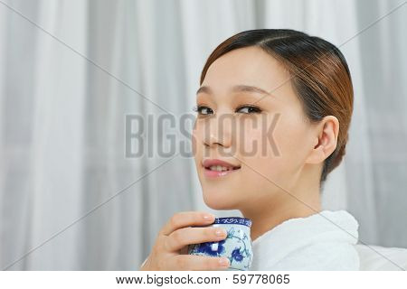 .a Young Woman With A Bathrobe Enjoying Tea.