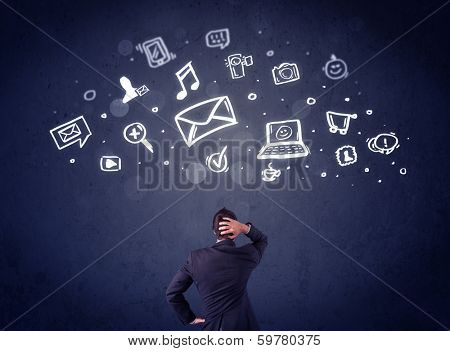 Young businessman sitting in office chair with sketched multimedia icons above his head