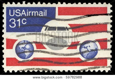 USA-CIRCA 1976: A 21 cent United States Airmail postage stamp, shows image of Plane and Globes on red white and blue background, circa 1976.