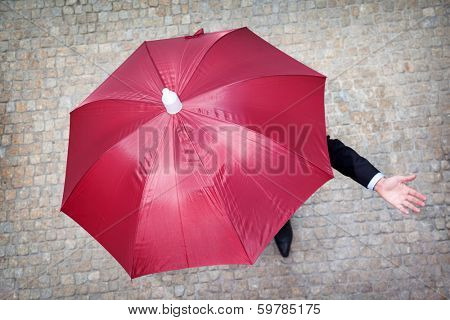 Businessman hidden under umbrella and checking if it's raining
