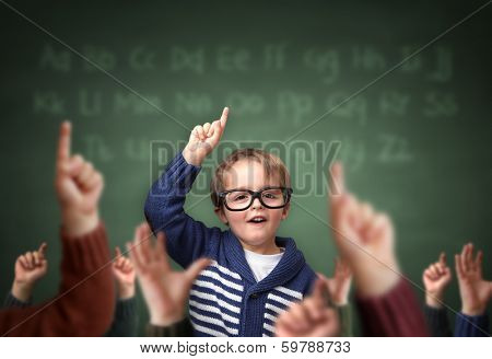 School child with hand raised in the classroom in front of a blackboard with other children concept  poster