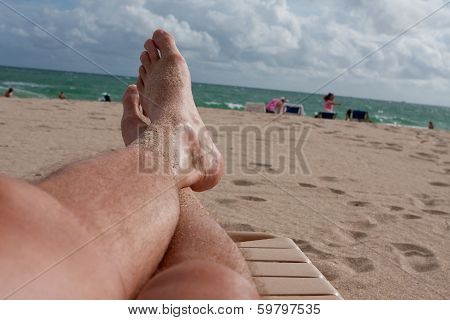 POV Man's Sandy Legs Stretched Out On Beach Lounge Chair