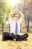 Young male businessman practicing yoga in a park
